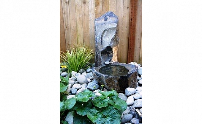 A narrow backyard area water feature