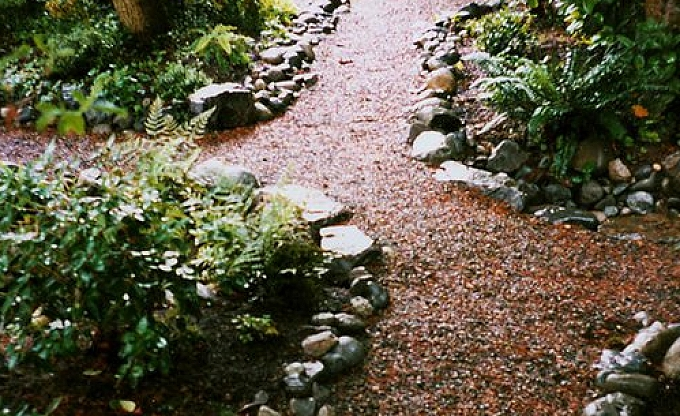 A typical woodland path, here a machine compacted crushed rock path, edged in washed river cobble, perhaps the best solution to creating a path through a native area.