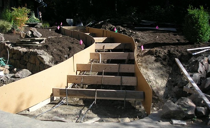 Before image of a poured concrete base form for mortared stone steps to be constructed.