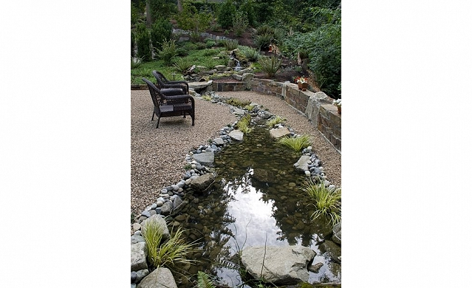 Stream area with ledge stone wall and inset stone accent.