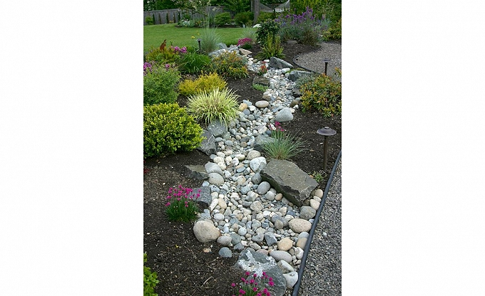 Typical dry stream treatment, an economical way to break up a bed for easier maintenance, transition drainage and offer a natural looking rock accent.