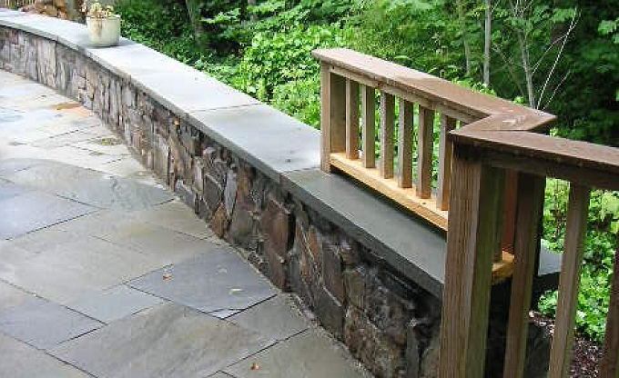 Mortared stone wall with seatcap and adjacent custom wood handrail.