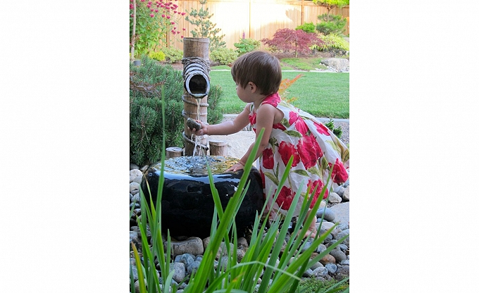 A client's grandchild enjoying innocent water play in the midst of an outdoor garden recently designed and installed by the team at Classic Nursery & Landscape. Spring is on the way!