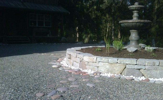 Center motor court fountain with raised planter, prior to planting. the stone is granite ledge. Note the inset compacted pancake rock, each segment pointing to the corresponding compass axis. Sostrom