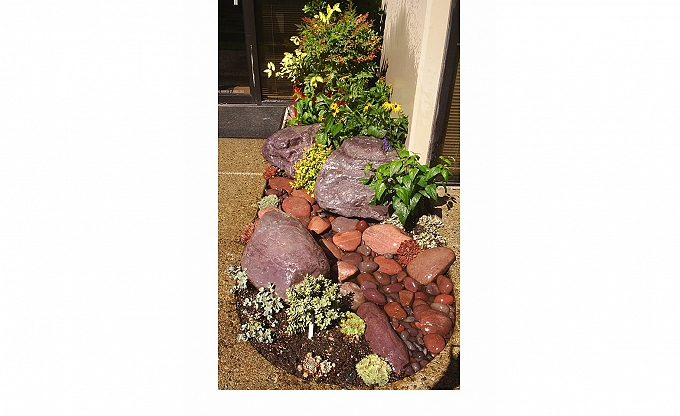 This little entry renovation might be under $500 with common river rock and basalt,  under $1K with custom specialty stone, like these naturally purple boulders available locally.