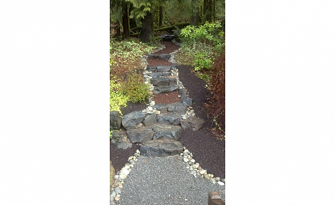 This simple woodland path with basalt, bark & river cobble edge. This may be available for as low as $3 per sf of path and $100 per step installed.