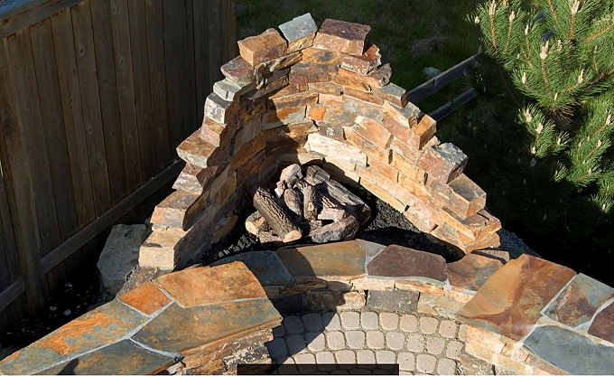 Stacked mortared stone backdrop for a corner firepit