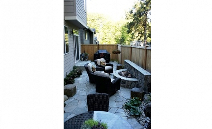Mortared stone firepit/seatwall in a narrow backyard in Redmond.