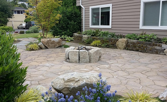 A raised granite wood firepit with a random set flagstone patio.