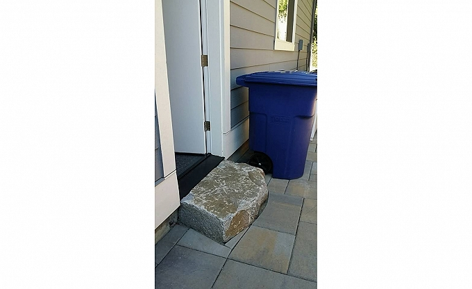 Small details matter, like this simple granite boulder step by the garbage cans...