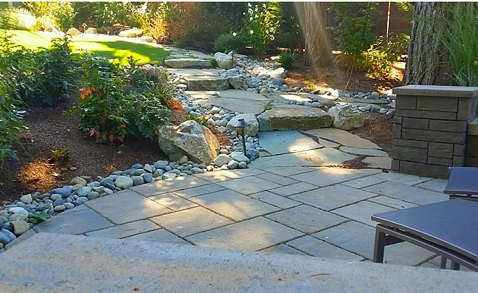 The transition from patio to flagstone, highlighting the steps up to the house